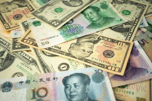 Pila del dollaro americano e banconote cinesi dello yuan sul tavolo