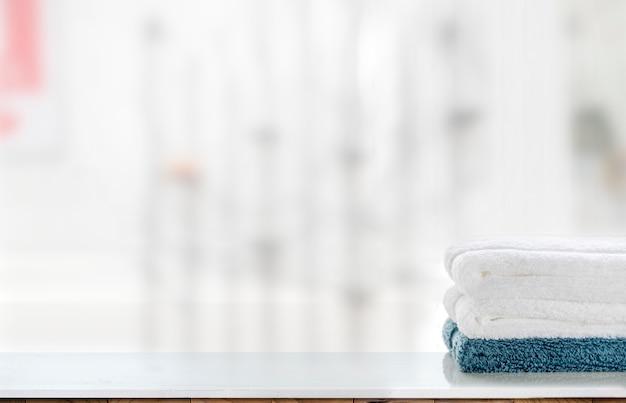 Pila del modello di asciugamani puliti sulla tavola e sul fondo bianchi della sfuocatura.