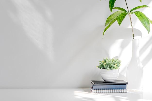 Pila del modello di libro e pianta da appartamento sulla tavola di legno bianca