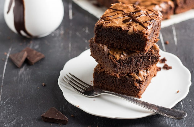 Pila del pezzo del dolce del brownie del cioccolato sulle pasticcerie casalinghe del piatto