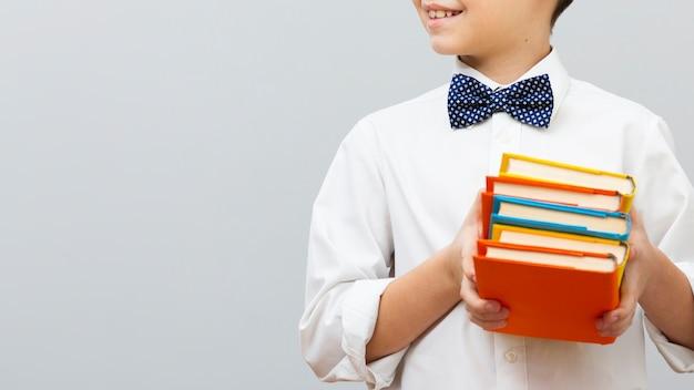 Pila della tenuta del ragazzo del primo piano di libri