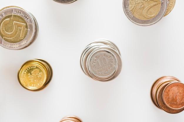 Pila di argento; oro; e monete di rame impilare su sfondo bianco