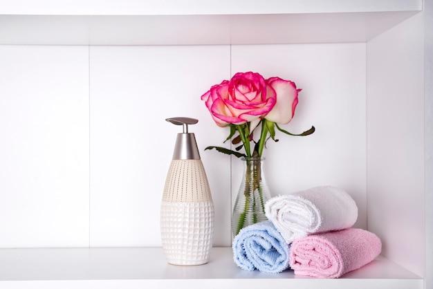 Pila di asciugamani con un dispenser di sapone e rose in vasein un primo piano del bagno