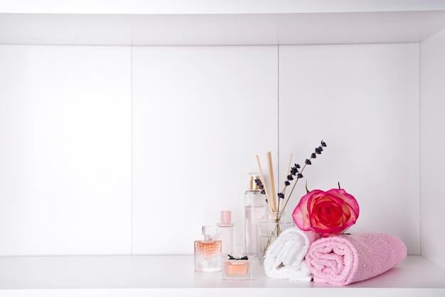 Pila di asciugamani da bagno con rosa e parfums su sfondo chiaro