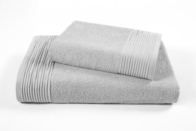 Pila di asciugamani di spugna, asciugamani grigi in pila sullo sfondo bianco