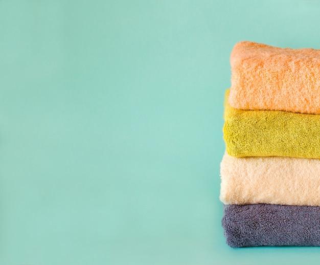 Pila di asciugamani di spugna su verde. giorno di bucato.