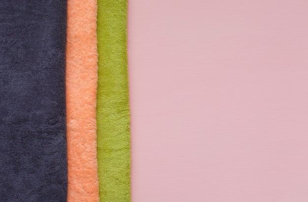 Pila di asciugamani di spugna sul rosa. giorno di bucato.