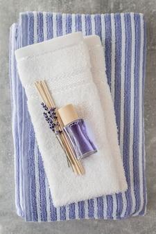 Pila di asciugamani morbidi e puliti con un mazzo di lavanda e deodorante per ambienti su grigio chiaro.