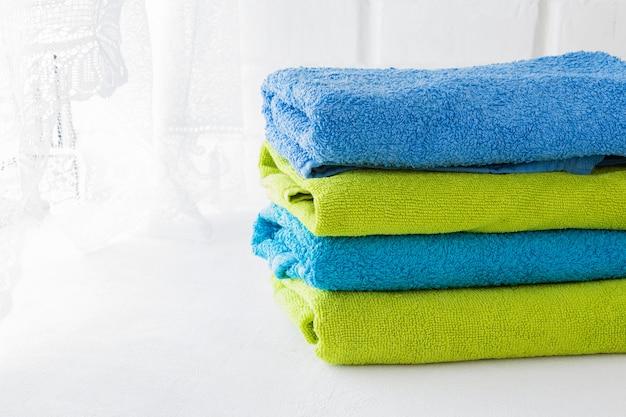 Pila di asciugamani morbidi puliti su sfondo bianco