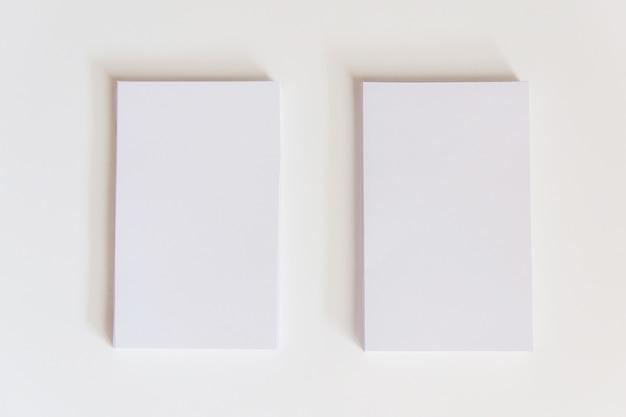 Pila di biglietti da visita bianchi vuoti. biglietti da visita del modello su fondo bianco con il percorso di ritaglio