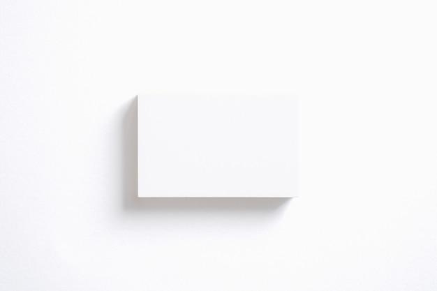 Pila di biglietti da visita in bianco isolata su bianco. modello per mostrare la tua presentazione.