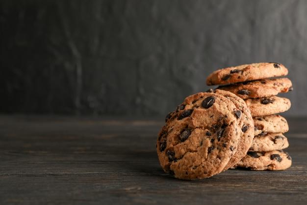 Pila di biscotti di pepita di cioccolato saporiti su di legno. spazio per il testo