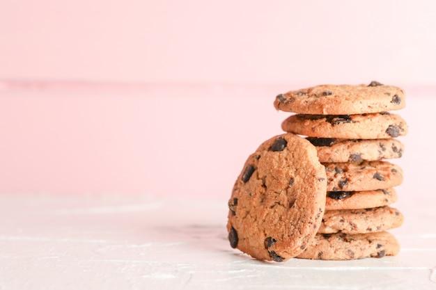 Pila di biscotti di pepita di cioccolato saporiti su fondo di legno. spazio per il testo