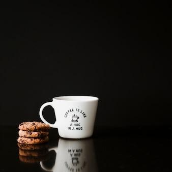 Pila di biscotti e tazza in ceramica su sfondo nero