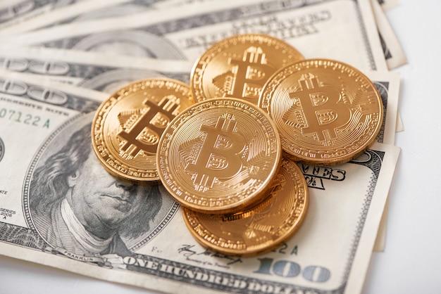 Pila di bitcoin dorati come la più popolare criptovaluta in tutto il mondo che giace sulle banconote in dollari e presenta denaro virtuale innovativo.