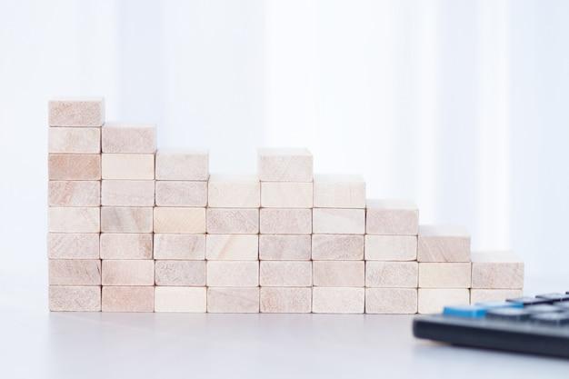 Pila di blocchi di legno, calcolatore su tutto il fondo di luce solare. abbassare, cadere, recessione, concetto di crisi.
