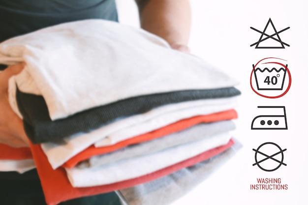 Pila di camicie piegate colorate con simboli di istruzioni di lavanderia