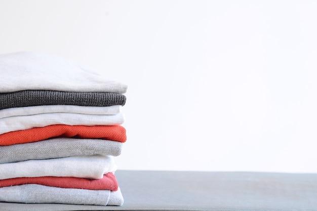 Pila di camicie piegate colorate sul tavolo grigio