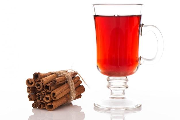Pila di cannella e un bicchiere di tè