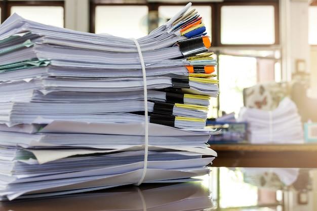 Pila di carta in ufficio, effetto riflesso del sole.