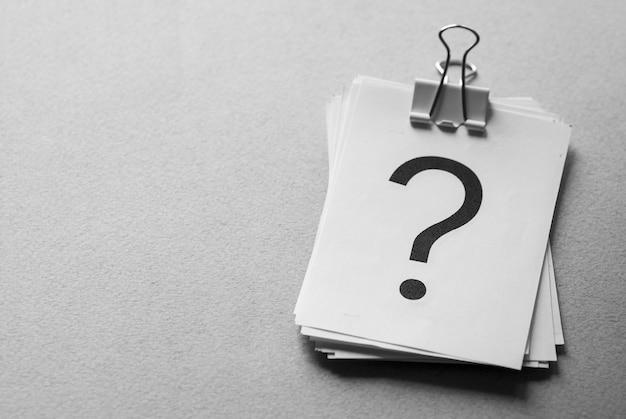 Pila di carte bianche stampate con punti interrogativi