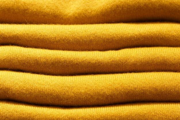 Pila di ceylon di tendenza giallo maglia a maglia maglioni close-up, trama, sfondo