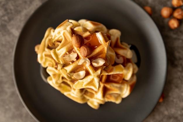 Pila di cialde sul piatto con miele e nocciole