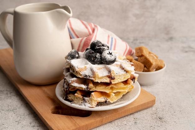 Pila di cialde sul piatto coperto di zucchero a velo e mirtilli