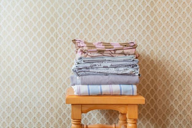 Pila di coperte delle lenzuola del tessuto su uno scaffale di legno