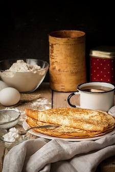 Pila di crepes e ingredienti per cucinare su un tavolo