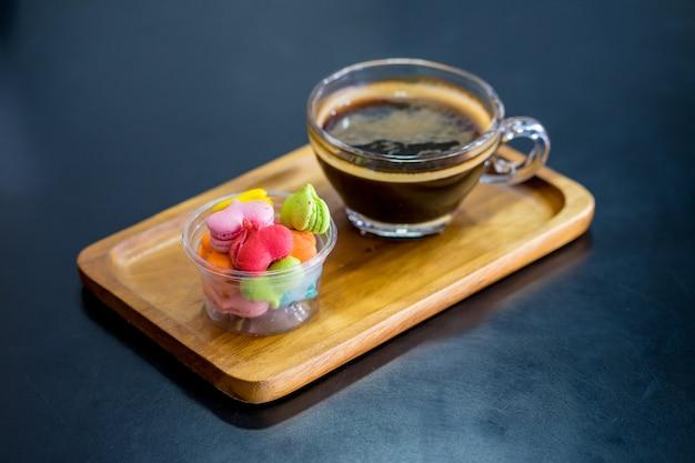 Pila di dessert di forma del cuore del macaron con la tazza di caffè sul piatto woodent