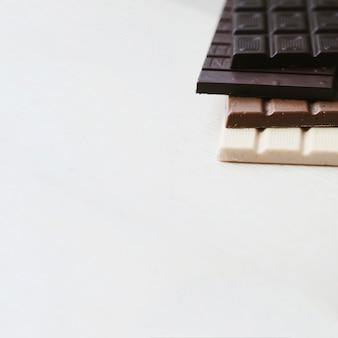 Pila di diverse barrette di cioccolato su sfondo bianco