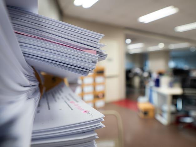 Pila di documento sulla tavola nella stanza dell'ufficio, concetto di affari