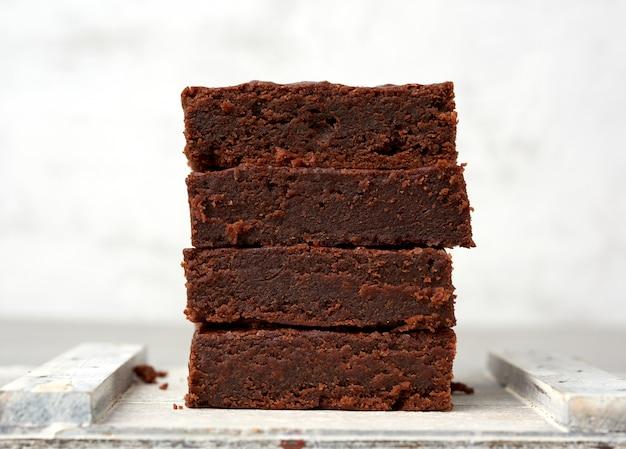 Pila di fette al forno quadrate del dolce di cioccolato del brownie