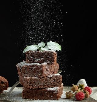 Pila di fette quadrate al forno del dolce di cioccolato del brownie spruzzate con zucchero bianco