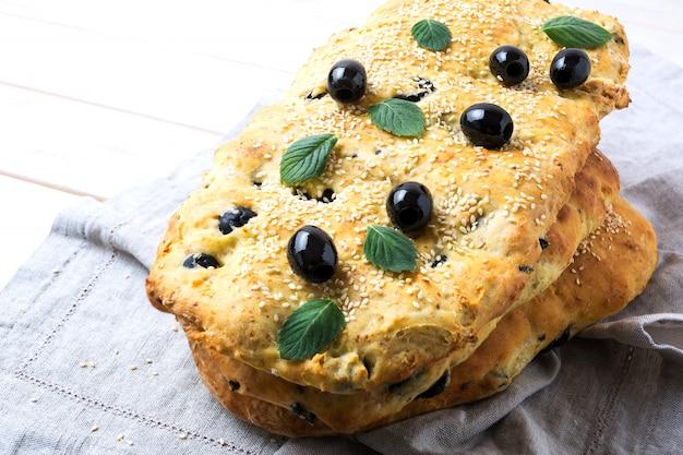 Pila di focaccia tradizionale italiana con olive, aglio ed erbe