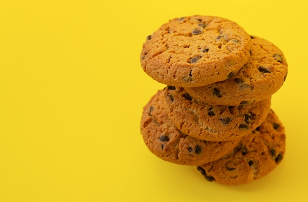 Pila di gustosi biscotti al cioccolato su sfondo giallo