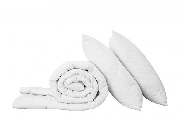 Pila di lenzuola su sfondo bianco, cuscino bianco sul piumone isolato,