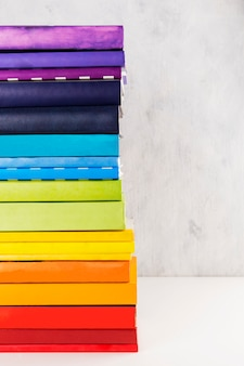 Pila di libri arcobaleno colorato su sfondo bianco. copia spazio
