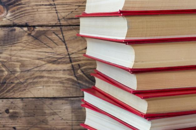 Pila di libri con copertina rigida su un tavolo di legno. copia spazio per il testo