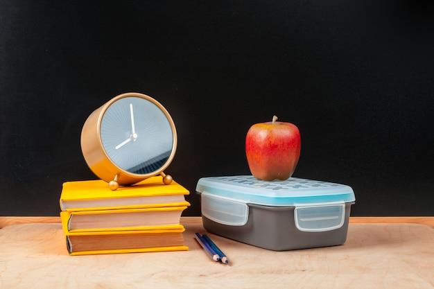 Pila di libri con la mela e la matita sulla tavola