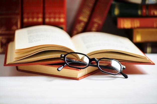 Pila di libri con occhiali da uomo neri messi sul libro aperto in biblioteca o sul tavolo bianco