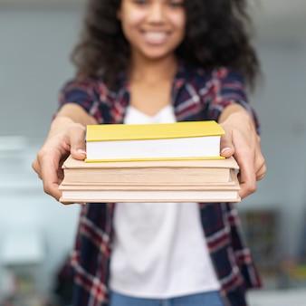 Pila di libri della holding della ragazza del primo piano