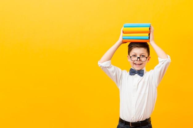 Pila di libri della tenuta del ragazzo dello copia-spazio