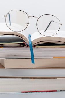 Pila di libri di angolo basso con gli occhiali in cima