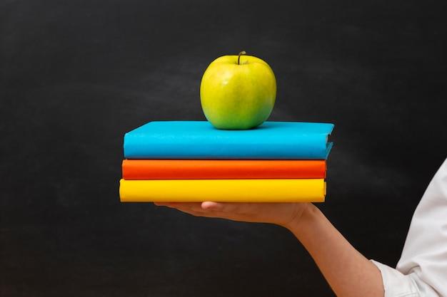 Pila di libri di vista frontale con la mela sulla cima