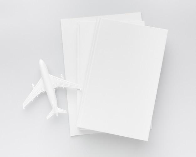 Pila di libri di vista superiore con l'aeroplano sullo scrittorio