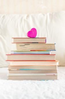 Pila di libri e cuore rosa sul letto bianco