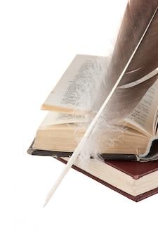 Pila di libri e penna isolato su sfondo bianco