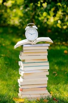 Pila di libri e sveglia sull'erba verde in autunno